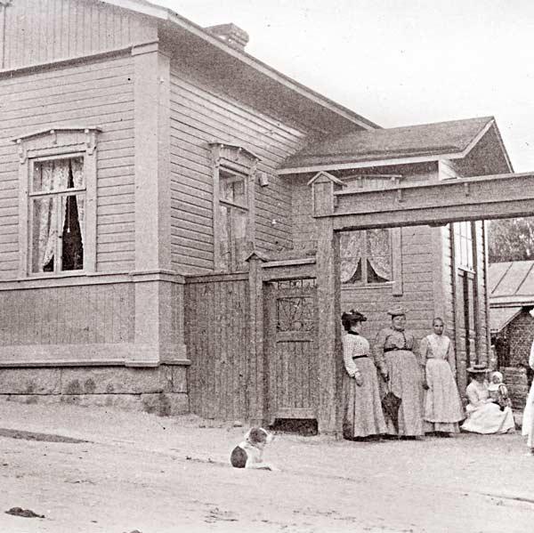 Seppä Herman Toivolan suunnittelema, vuonna 1890 valmistunut asuinrakennus osoitteessa Cygnaeuksenkatu 2. Rakennuksen eteen on kerääntynyt tontin naisväkeä, päivänvarjon kanssa rouva Matilda Toivola. Kuva: Keski-Suomen museo