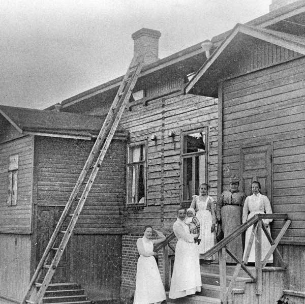 Synnytyssairaalan henkilökuntaa yhteiskuvassa Matilda Toivolan (yläportaalla keskellä) kanssa Jyväskylän yksityisen synnytyssairaalan rappusilla Cygnaeuksenkatu 2:ssa 1900-luvun alussa. Rakennus valmistui vuonna 1897 Herman Toivolan rakennuttamana ja jyväskyläläisen Oskari Toikan suunnittelemana. Kuva: Keski-Suomen museo.